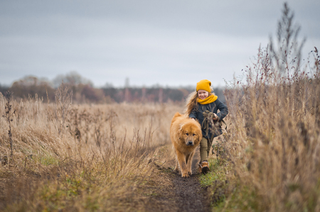 The girl walking with the loyal good dog two times...