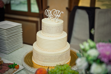 Three-tiered white-and-beige cake for the wedding. Stock Photo