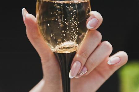 彼の手にシャンパンのグラス。