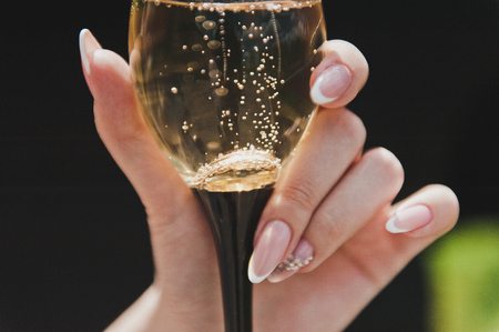 A glass of champagne in his hand.