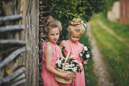 Two little bridesmaid standing at the wicker fence.