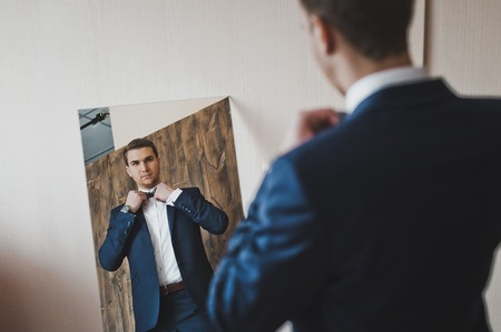 The man looks in the mirror.