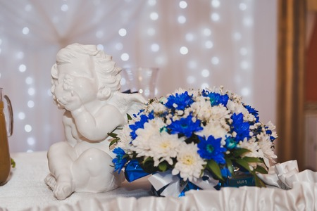 The figure of an angel near the bouquet of white and blue flowers.