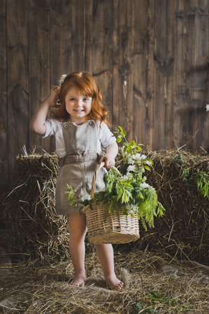 Portrait of a redhead little girl with a basket.