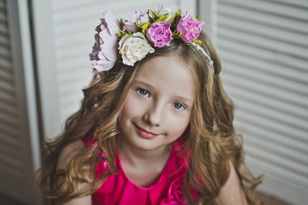 Spring girl wearing a wreath of flowers on the background shutter.