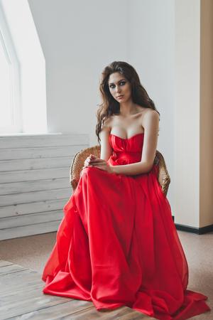 Mooi meisje met rode lange jurk. Stockfoto