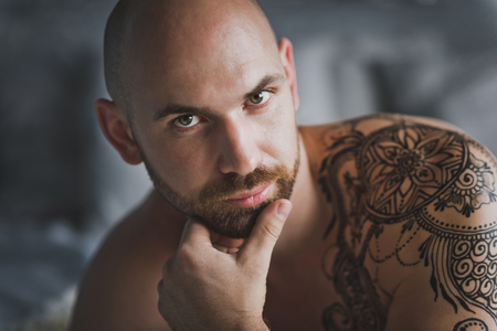 Close-up portrait of a bald brutal man with a beard.