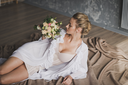 Beautiful woman in white nightie lying on the bed and a bouquet of flowers.