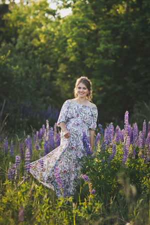 Beautiful portrait of a girl standing in the field of blooming Lupin. Stockfoto