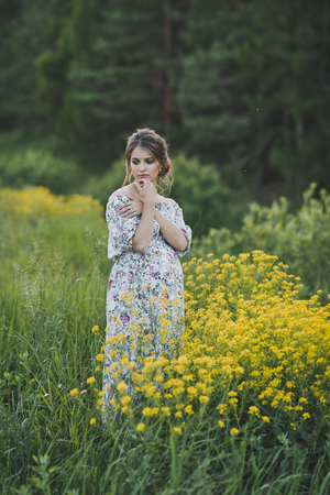 The girl on a glade of yellow flowers.