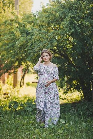 Portrait of a pregnant girl walking in the summer garden.
