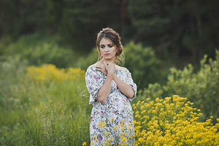 A beautiful portrait of a pregnant girl in a long dress standing near a clearing with yellow small flowers.