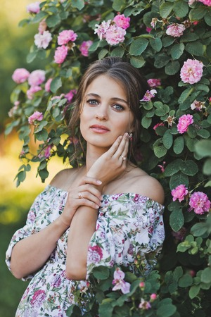 Girl on the background of a Bush with lilac flowers.