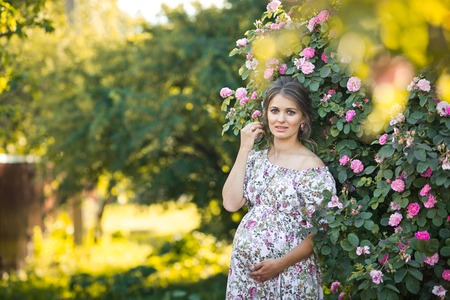 The girl in the position of pregnancy in nature in a free colorful dress.