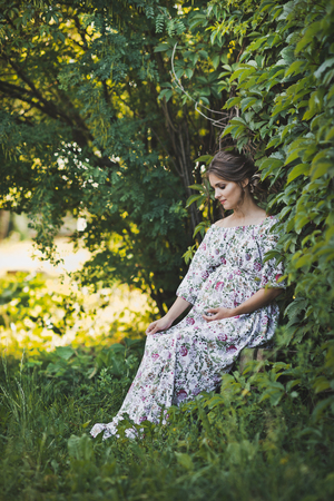 Portrait of a pregnant girl walking in the summer garden.