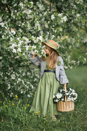 A little girl walks through the blooming garden. Reklamní fotografie