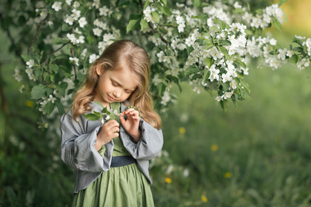 Large portrait of a child in a hat among the flowers of cherries. Stock Photo - 112103604