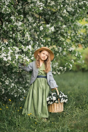 A little girl walks through the blooming garden. Reklamní fotografie