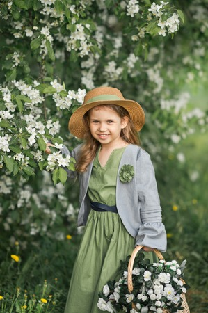 A little girl in a simple dress with a basket of white violets. Stockfoto