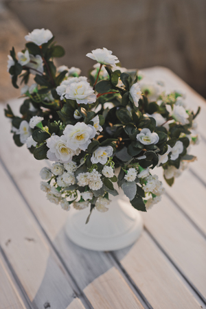Small bouquet of mock orange on the table of the white boards.
