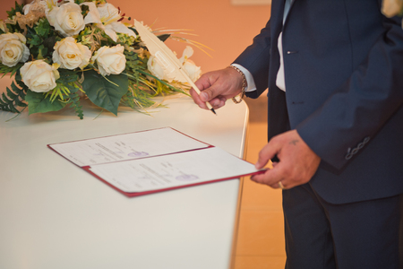 The process of signing an important document with a pen.
