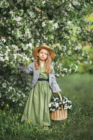 A little girl walks through the blooming garden. Stockfoto