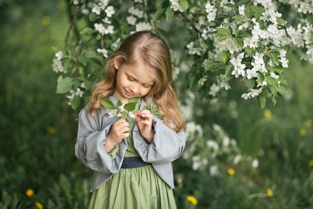 Large portrait of a child in a hat among the flowers of cherries. Standard-Bild - 112103903