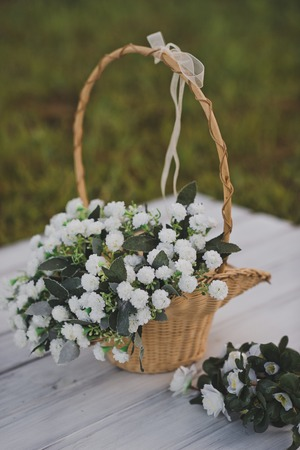 Wicker basket with a handle and a bouquet of white violets. 免版税图像 - 112103925
