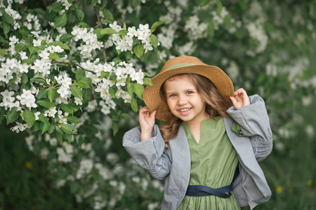 Large portrait of a child in a hat among the flowers of cherries.
