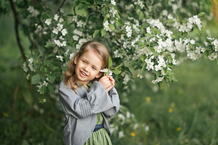 Large portrait of a child in a hat among the flowers of cherries. 스톡 콘텐츠 - 111391544