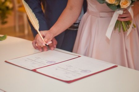 A woman signs a document with a pen. Stockfoto