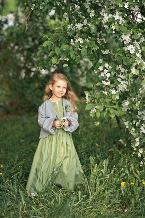 A little girl in a simple dress with a basket of white violets. Reklamní fotografie