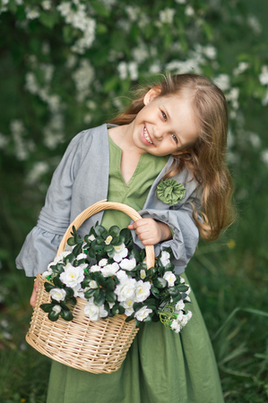 Happy young girl carries a basket of flowers.