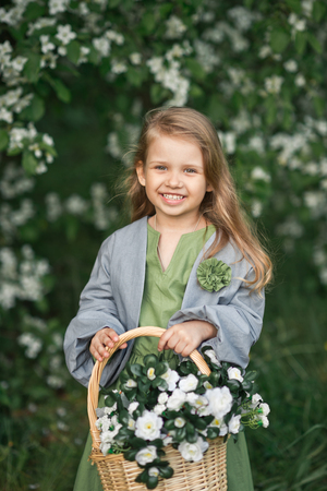 Happy young girl carries a basket of flowers. Reklamní fotografie - 112123239
