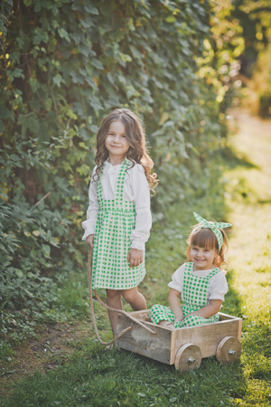 Two sisters play outside with a cart.