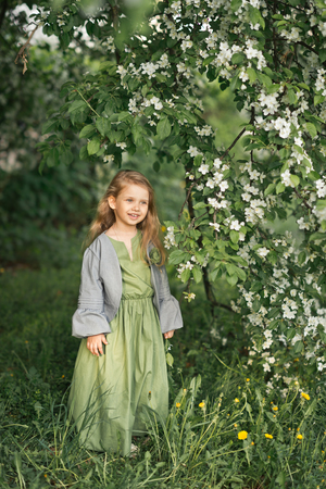 Portrait of a little girl in the spring in the flowering trees. Reklamní fotografie