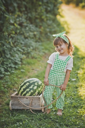 Portrait of a child with a huge watermelon in the cart. Reklamní fotografie - 112123268