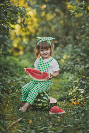 A happy child eats a juicy slice of watermelon.