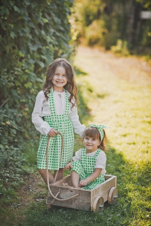 Two sisters play outside with a cart. Stock Photo - 112119686