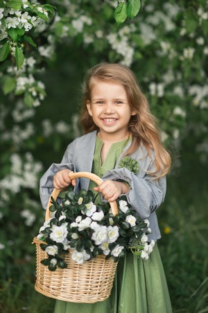 The child enjoys the spring and a basket of flowers in his hands. Standard-Bild - 112119687