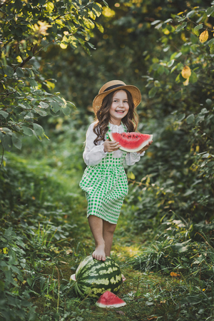 Smiling child with a piece of juicy watermelon in his hands.