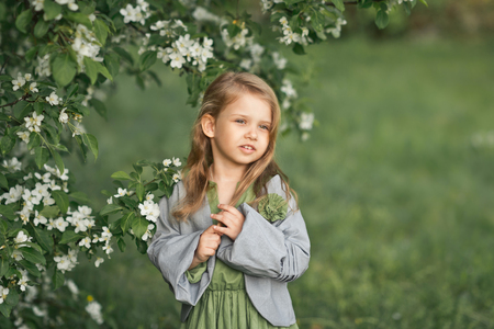 The child stands near a flowering cherry Bush. Фото со стока - 112119692