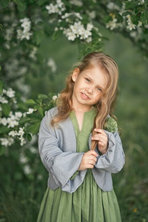 The child stands near a flowering cherry Bush.