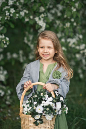 The child enjoys the spring and a basket of flowers in his hands. Stockfoto