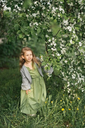 Portrait of a little girl in the spring in the flowering trees. Stockfoto