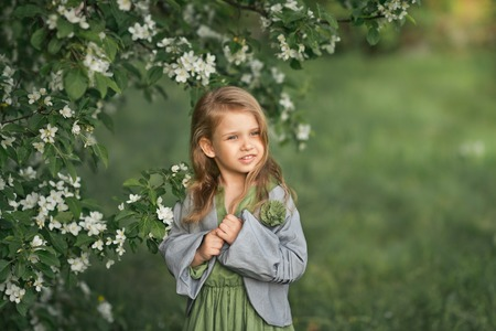 The child stands near a flowering cherry Bush. Фото со стока - 112120840