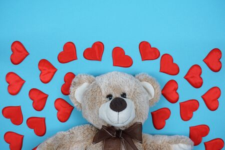 Teddy bear with red hearts on a blue background. Concept for Valentine's Day. Foto de archivo