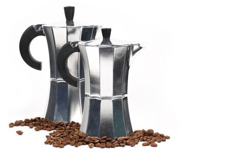 A metallic, shiny retro coffee pot on an isolated white background surrounded by coffee beans. Copy space.