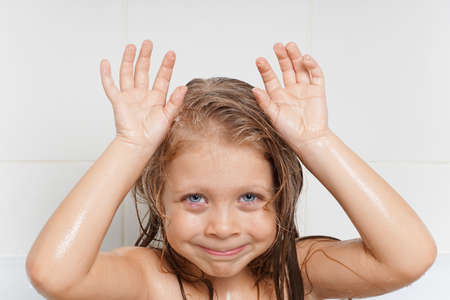 Cute, beautiful, cheerful little girl with long hair in the bathroom. Children's emotions with soap bubbles. Children's hygiene. Water games. Hygiene of the child. Health