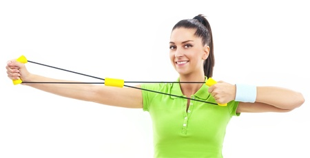 Young beautiful woman during fitness with expander photo